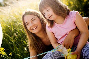 crianca com sindrome de donw feliz segurando um balao
